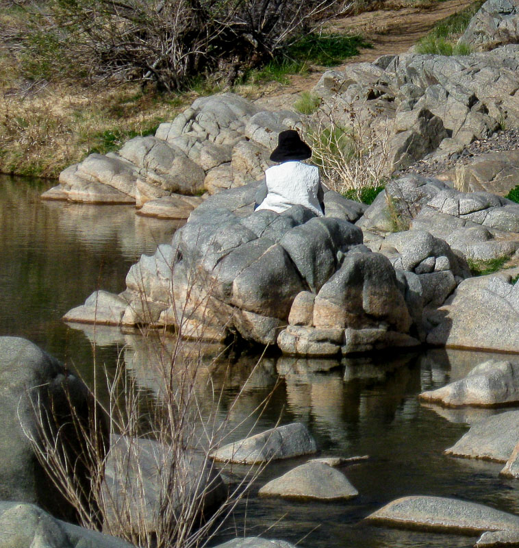 Woman resting on a large section or rocks