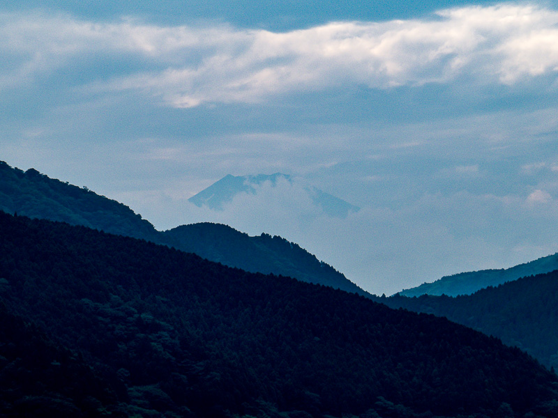 Mt. Fuji peaking from behind the mountains and clouds