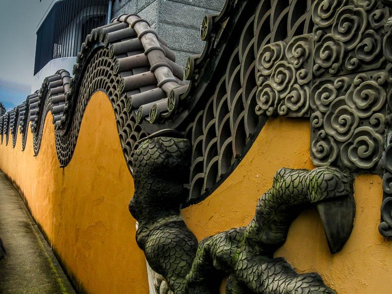 Dragon statue on parking area wall near Glover Garden, Nagasaki