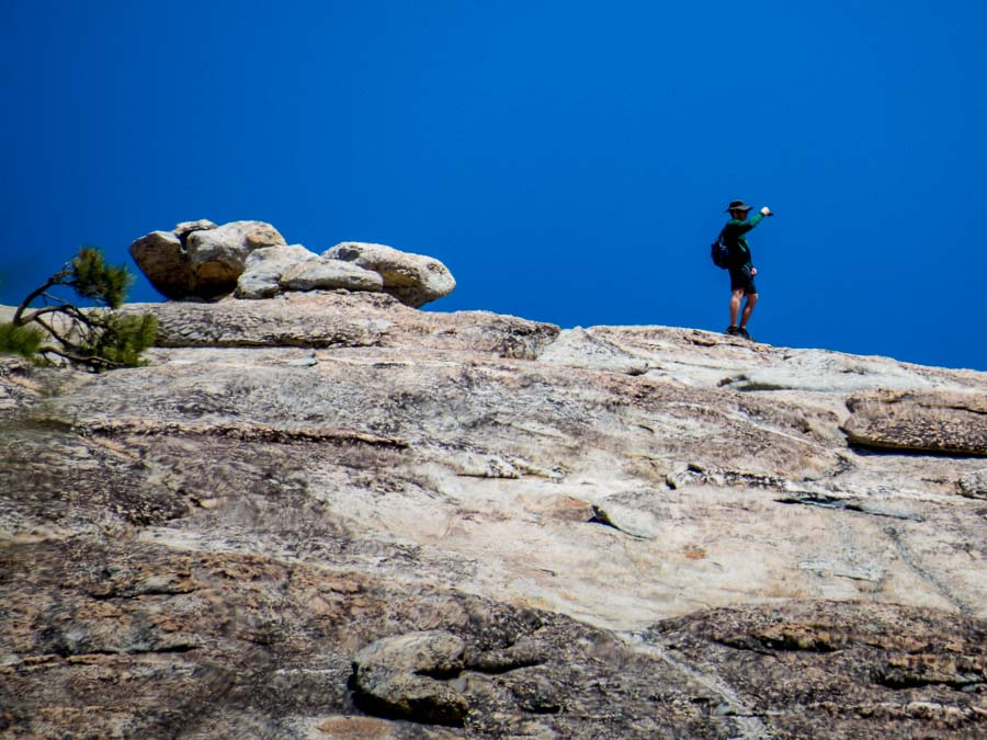A hiker standing on top of Sentinel Dome stops to take a picture