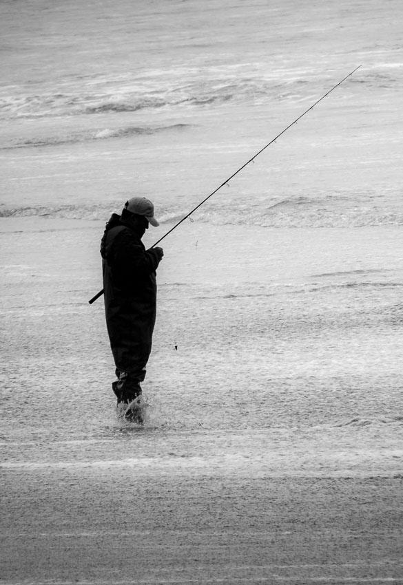 A surf caster adjusting his rig<