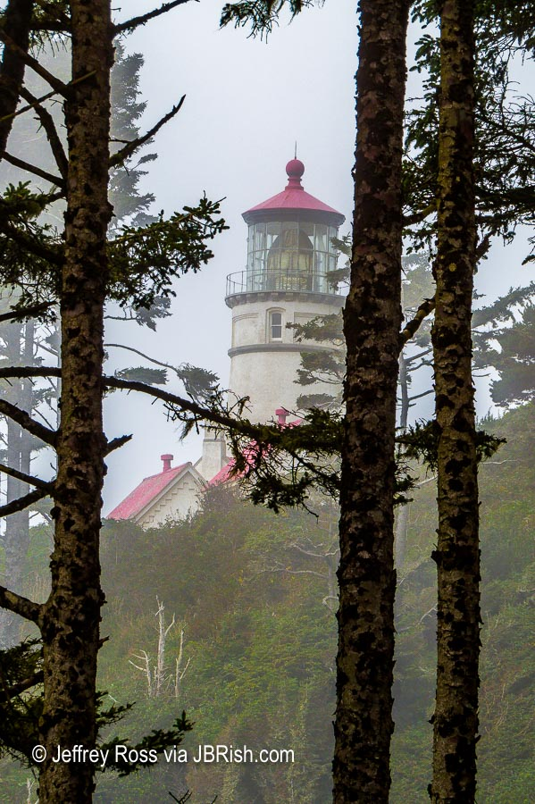 The lighthouse becomes visible through the trees as we walk