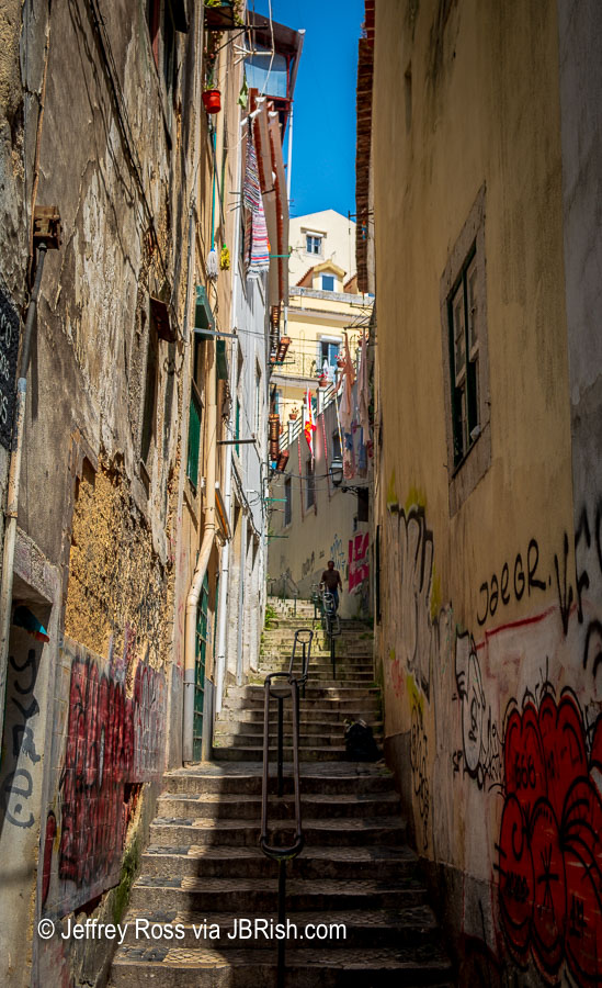 Narrow alleyway stairs with graffiti
