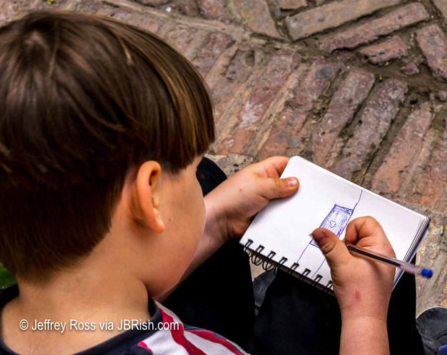 Young boy drawing in the courtyard