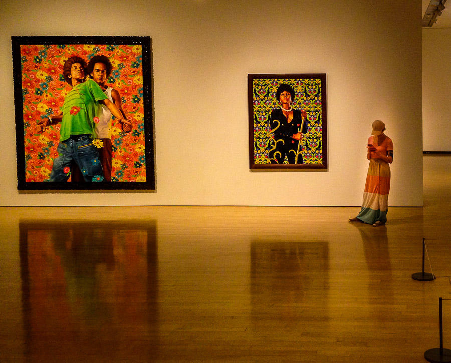 Young woman in colorful dress checking phone at the art museum