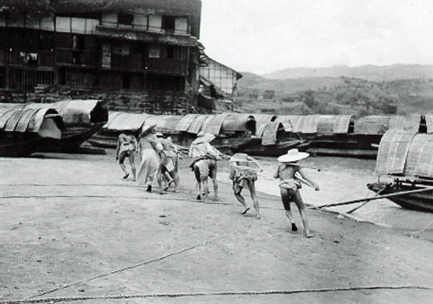 A group of Chinese men pull a sampan along the inlet or river way